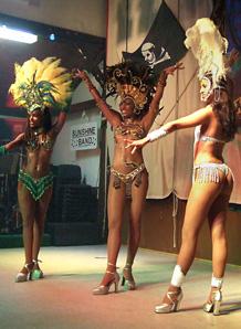 Drei leichtbekleibete brasilianische Tänzerinnen mit ausladendem Kopfschmuck aus Federn